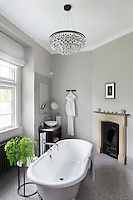 A  contemporary ensuite bathroom with a mosaic floor still retains a small period fireplace