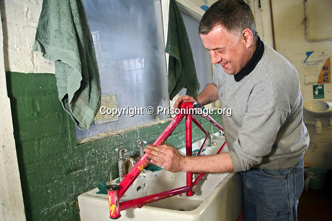 An inmate working to recondition an old bicycle in the Inside Out trust workshop. HMP Liverpool, Merseyside, United Kingdom. Inmates at HMP Liverpool will work during the day in industrial workshops, or doing laundry and other such tasks.