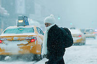 A woman crosses a street under the snow during the pass of the winter storm JONAS, in New York, 01/23/2016. Photo by VIEWpress