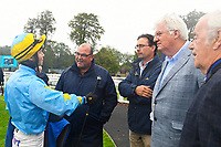 Jockey William Cox talks through the race with trainer Roger Teal and connections in the Winner's enclosure after winning The Champagne Joseph Perrier Confined Handicap during Horse Racing at Salisbury Racecourse on 14th August 2019
