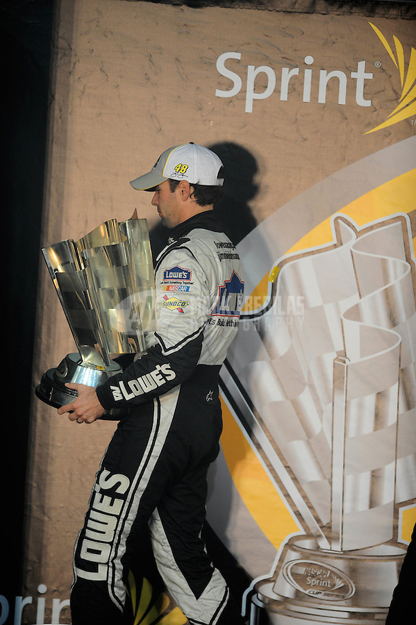 Nov. 16, 2008; Homestead, FL, USA; NASCAR Sprint Cup Series driver Jimmie Johnson carries the trophy off stage after winning the 2008 championship following the Ford 400 at Homestead Miami Speedway. Mandatory Credit: Mark J. Rebilas-