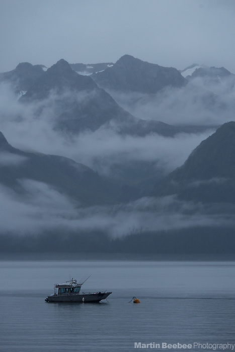 Fishing boat below misty mountains on Resurrection Bay, Seward, Alaska