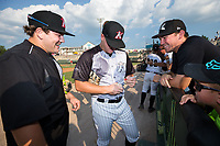 Jake Burger (left) of the Kannapolis Intimidators and Keegan Maronpot (right) of the Wake Forest Demon Deacons smile as they watch Gavin Sheets (center) autograph a baseball for a fan at Kannapolis Intimidators Stadium on July 22, 2017 in Kannapolis, North Carolina.  The Fireflies defeated the Intimidators 4-0.  (Brian Westerholt/Four Seam Images)