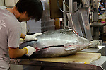 Japanese fish butcher cuts into a tuna at Tsukiji Fish Market Tokyo Japan