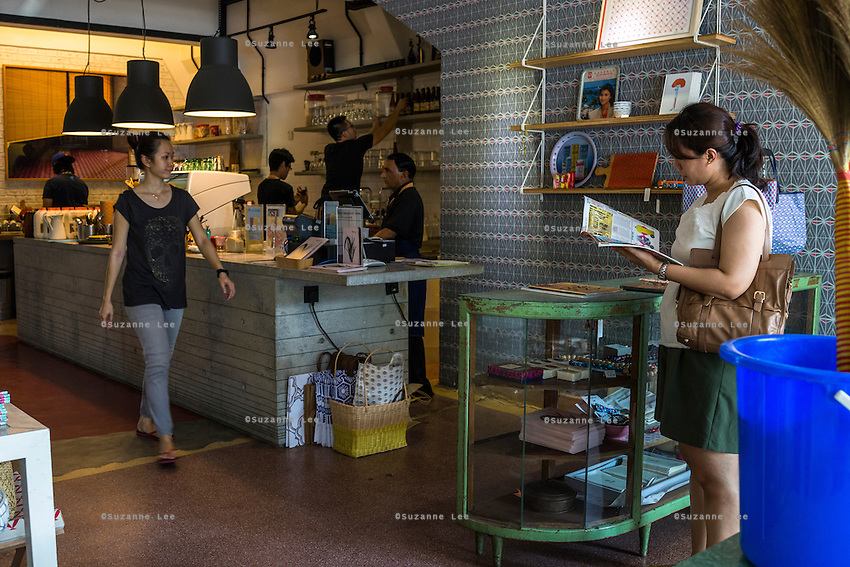 Staff work as a customer browses a magazine in DR.inc cafe and Nala Designs in Bangsar, Kuala Lumpur, Malaysia, on 18 August 2015. Nala Designs, by founder and designer Lisette Scheers, is inspired by Malaysia's melting pot of Chinese, Malay and Indian cultures. Photo by Suzanne Lee for Monocle