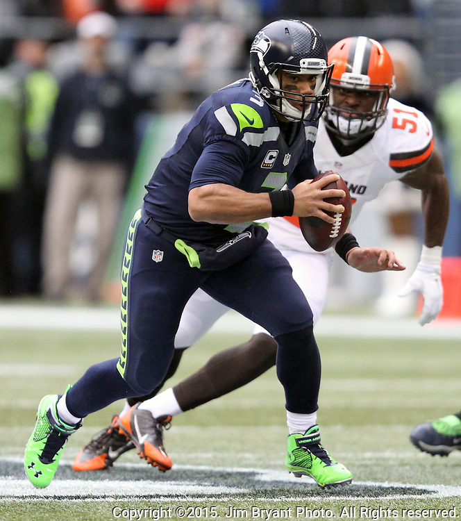 Seattle Seahawks quarterback Russell Wilson (3) scrambles for a first down against Cleveland Browns linebacker Barkevious Mingo (51) at CenturyLink Field in Seattle, Washington on December 20, 2015. The Seahawks clinched their fourth straight playoff berth in four seasons by beating the Browns 30-13.  ©2015. Jim Bryant Photo. All Rights Reserved.