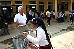 "Vietnam War veteran Mark Oconnor stands in front of a school in the rural highlands district of A Luoi, Vietnam, as a girl rides past on a new bicycle that he gave her. Oconnor, who served in the war from 1970 to 1971, recently bought 55 bicycles for ethnic minority students in the district who live too far from school to walk there every day. ""I took too much the first time I was over here, and now I am trying to give back,"" said Oconnor, 63, of Sioux Falls, S.D. ""It probably won't ever be enough, but I want to do what I can."" Oconnor said he plans to return to Vietnam next year and give away at least 200 more bicycles to poor children. April 21, 2014."