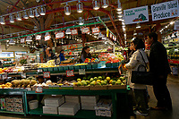 People shopping at a  fruit and produce vendor inside the Granville Island Public Market, Vancouver, British Columbia, Canada