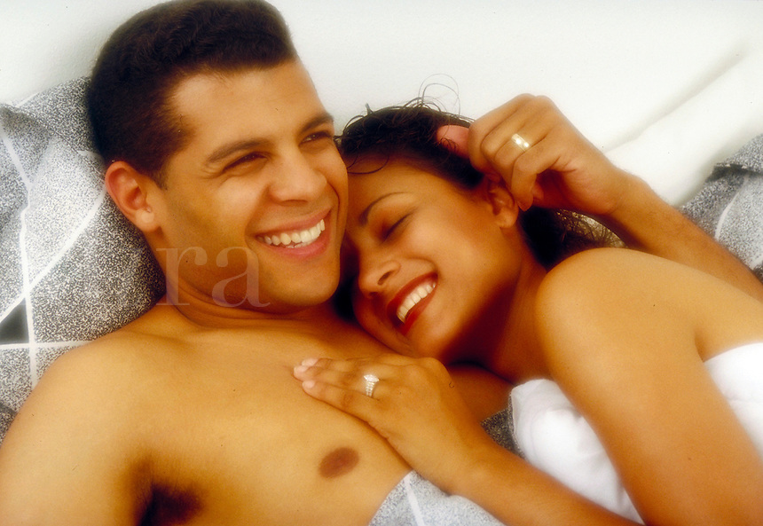 Young ethnic playful couple enjoying late morning in bed. Young ethnic couple. Houston Texas USA.