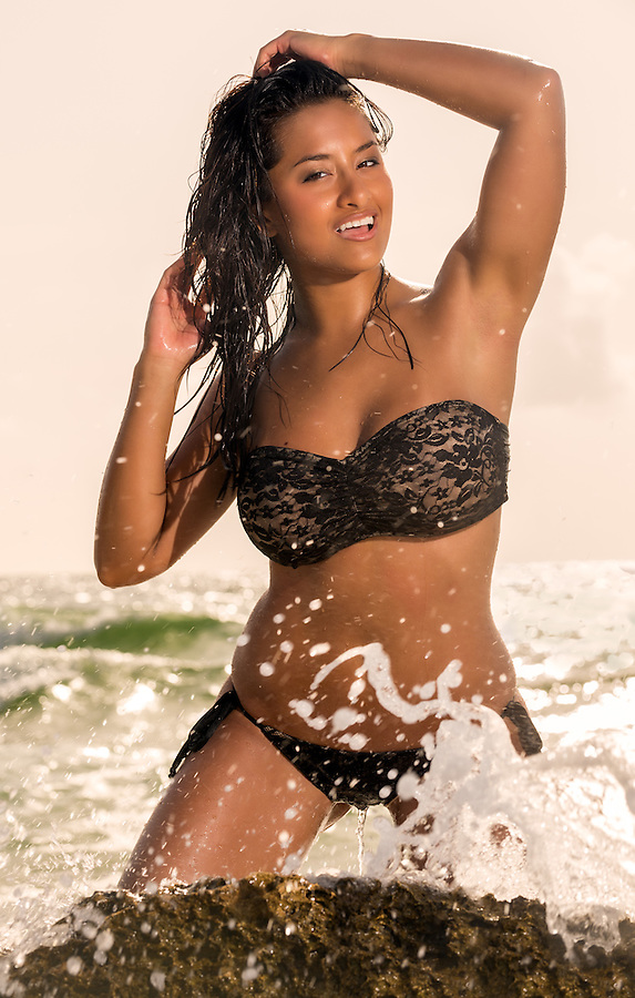 Close up portrait of young hot model posing in the beach with ocean splashing behind her