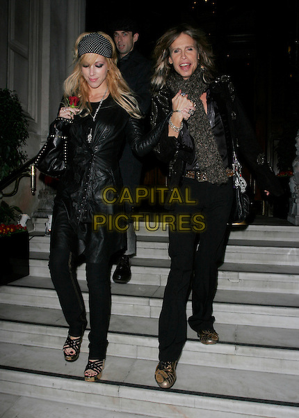 STEVEN TYLER & GUEST.Leaving the Mandarin Oriental Hotel, where he is staying whilst his band Aerosmith play dates of their word tour, Knightsbridge, London, England, February 19th 2007..full length black jacket leather trousers head scarf long hair scarf red rose flower.CAP/AH.©Adam Houghton/Capital Pictures.