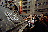 "Bucharest, Romania<br /> December 1989<br /> <br /> A captured member of Ceausescu's Securitate is taken away in an armored personal carrier surrounded by acrowd seeking revenge.<br /> <br /> The week-long series of violence that overthrew the Communist regime of Nicolae Ceausescu, ended in a trial and execution of Ceausescu and his wife Elena by firing squad. Romania was the only Eastern Bloc country to violently overthrow its Communist regime or to execute its leaders.<br /> <br /> The Romanian populace was dissatisfied with the Communist regime and leader Ceausescu's economic and development policies were blamed for the country's shortages and widespread poverty. The powerful secret police (Securitate) controlled what was essentially a police state. Ceausescu was not pro-Soviet but ""independent"" on foreign policy. He imitated the hard-line, megalomania, and personality cults of communist leaders like North Korea's Kim Il Sung."