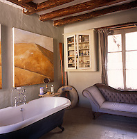 A bathroom with an exposed beam ceiling and stone tiled floor.  A painting hangs above a free-standing roll top bath and an upholstered chaise longue is placed beneath a window.