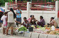 Women sell vegetables on a sidewalk in Dili, Timor-Leste (East Timor)