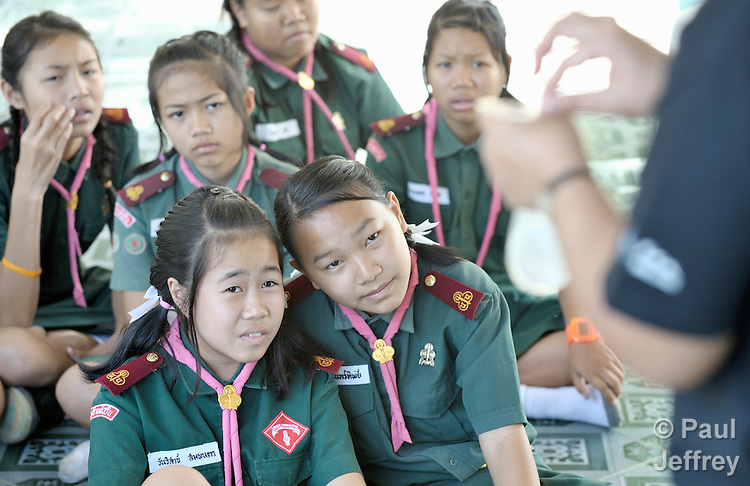 Wearing their scouting uniforms, girls in the village of Toong-sa-tok in northern Thailand learn about HIV and AIDS during a session at the temple-supported Banhuarin School. Here they watch an HIV positive woman demonstrate how to use a female condom.