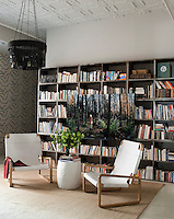 The library features a wall papered in a print by Neisha Crosland and a photograph by Ellen Kooi is displayed in front of modular metal book shelves