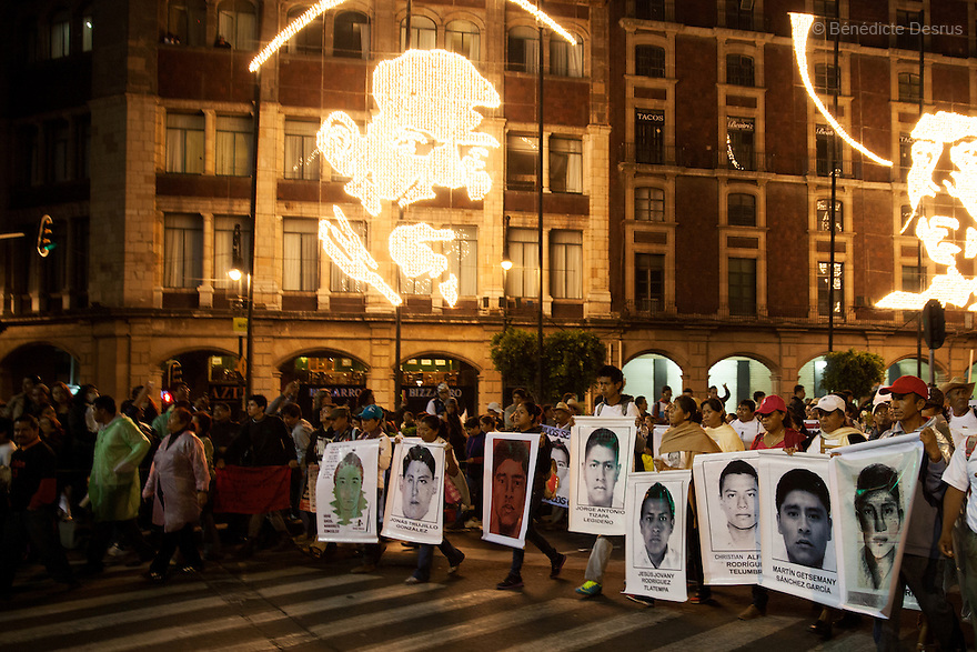 Parents and relatives of the 43 missing students from Ayotzinapa's teacher training college, hold images of the missing students, during a massive march  in Mexico City, Mexico on November 20, 2014. Caravans of students and family members of 43 missing Ayotzinapa's students converged on the capital after several days crisscrossing the country. Parents of the 43 missing students still do not believe the official line that the young men are all dead. Criticism of the government has intensified in Mexico and the country has been convulsed by protests. Many are demanding justice and that the search for the 43 missing students continue until there is concrete evidence to the contrary. Mexico officially lists more than 20 thousand people as having gone missing since the start of the country's drug war in 2006, and the search for the missing students has turned up other, unrelated mass graves. (Photo by Bénédicte Desrus)