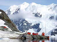 The Almirante Brown research station (base) in Paradise Harbor (aka Paradise Bay), Antarctica. The Almirante Brown base belongs to Argentina. Snow covered mountains and a glacier are in the distance.