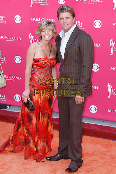 LORI & RICHIE MacDONALD.The 43rd Annual Academy of Country Music Awards (ACM) held at MGM Grand Garden Arena, Las Vegas, Nevada, USA, .18 May 2008 .full length married husband wife red orange print dress brown suit.CAP/ADM/MJT.©MJT/Admedia/Capital Pictures