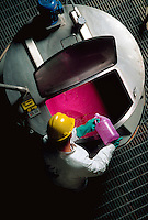 Overhead shot of paper plant worker pouring dye into vat