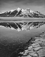 Black & white of Ice breakup on McDonald Lake shore in early spring & peaks in background,GLACIER NATIONAL PARK, Montana