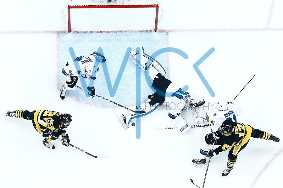 Martin Jones #31 of the San Jose Sharks makes a save in front of Nick Bonino #13 and Carl Hagelin #62 of the Pittsburgh Penguins in the second period during game five of the Stanley Cup Final at Consol Energy Center in Pittsburgh, Pennsylvania on June 9, 2016. (Photo by Jared Wickerham / DKPS)