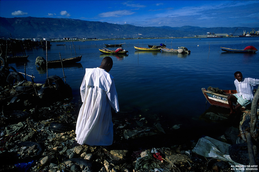A protestants minister enters the water along the edge of Cite Soleil for a baptism ceremony in Port-au-Prince, Haiti on Sunday, September 3, 2000. Protestant, Catholic and Voodoo religions are practiced in Haiti.