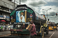 "Nigeria. Enugu State. Enugu. Town center. Traffic stopped at red light. A truck is carrying clean water supply. The tank is covered with religious precepts ( Holy Spirit is my power. To God be the glory) and a drawing with Jesus Christ (I drank this cup for your sake). An Igbo man works as a street seller and walks in the middle of the cars. He carries a cardboard box in his arms with   sweets to be sold. Two yellow auto rickshaw used by ""Keke"" drivers for transporting people around town. The  tricycle better known in Nigeria as the Keke NAPEP is gaining the dominance on Nigerian roads sweeping every street of cities and villages. The auto rickshaw is a common form of urban transport, both as a vehicle for hire and for private use. Enugu is the capital of Enugu State, located in southeastern Nigeria. 5.07.19 © 2019 Didier Ruef"