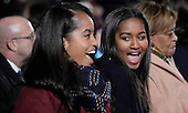 First daughters Malia Obama, left, and Sasha Obama, right, smile during the National Christmas tree lighting ceremony on the Ellipse south of the White House December 3, 2015 in Washington, DC. The lighting of the tree is an annual tradition attended by the President and the first family.<br /> Credit: Olivier Douliery / Pool via CNP