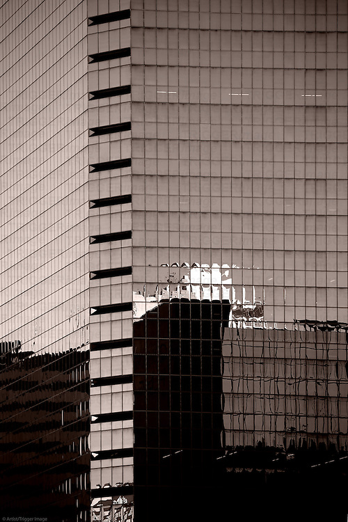 Abstract reflections of surrounding buildings in the glass facade of a modern skyscraper.