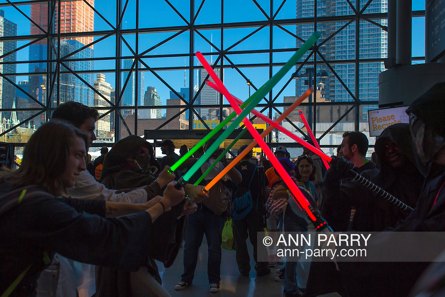 Manhattan, New York City, New York, USA. October 10, 2015. Cosplayers have a mock duel with colorful toy light sabers at the 10th Annual New York Comic Con. NYCC 2015 is expected to be the biggest one ever, with over 160,000 attending during the 4 day ReedPOP event, from October 8 through Oct 11, at Javits Center in Manhattan