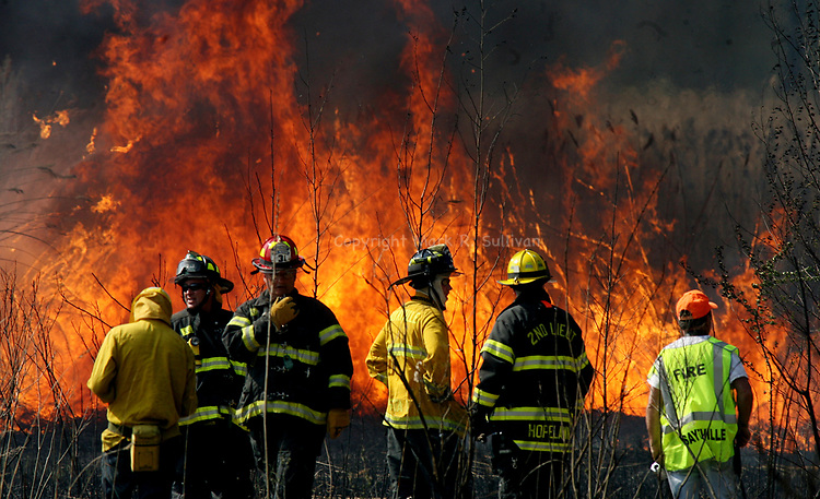 Firefighters work on battling a strong brush fire in Sayreville behind Weber Ave.<br /> <br /> METRO<br /> 10544<br /> ON SUN APR 11,2010<br /> MARK R. SULLIVAN/CHIEF PHOTOGRAPHER