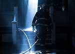 A FDNY Battalion Chief stands in a ray of light during s fire on the first floor of a 5 story multiple dwelling at 644 Rockaway Parkway on Monday, Feburary, 12.