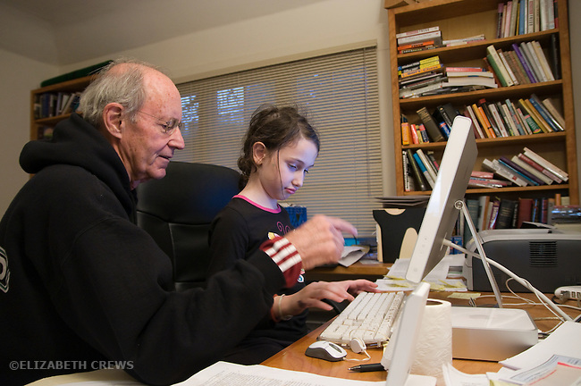 Berkeley CA  Grandfather, seventy-six, helping granddaughter, eight-years-old work on his computer  MR