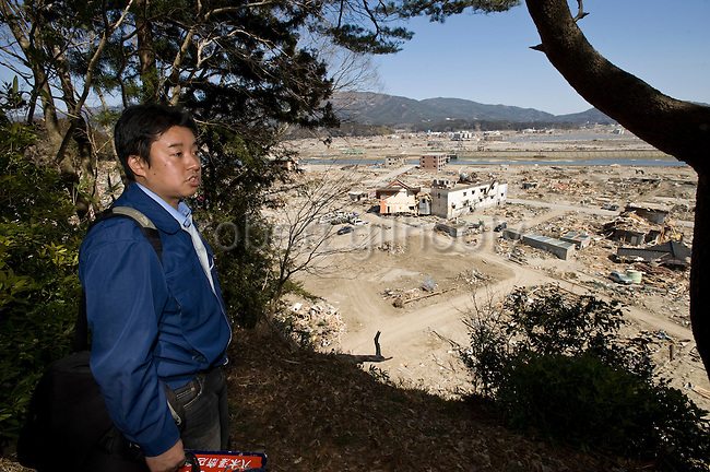 Michihiro Kohno, president of soy sauce and miso soup maker Yagisawa Shoten, looks over the wreckage that includes his family's 207-year-old company from a hill where he guided his staff and other residents to safety in Rikuzentakata, Iwate Prefecture, Japan on 06 April, 2011. .Photographer: Robert Gilhooly