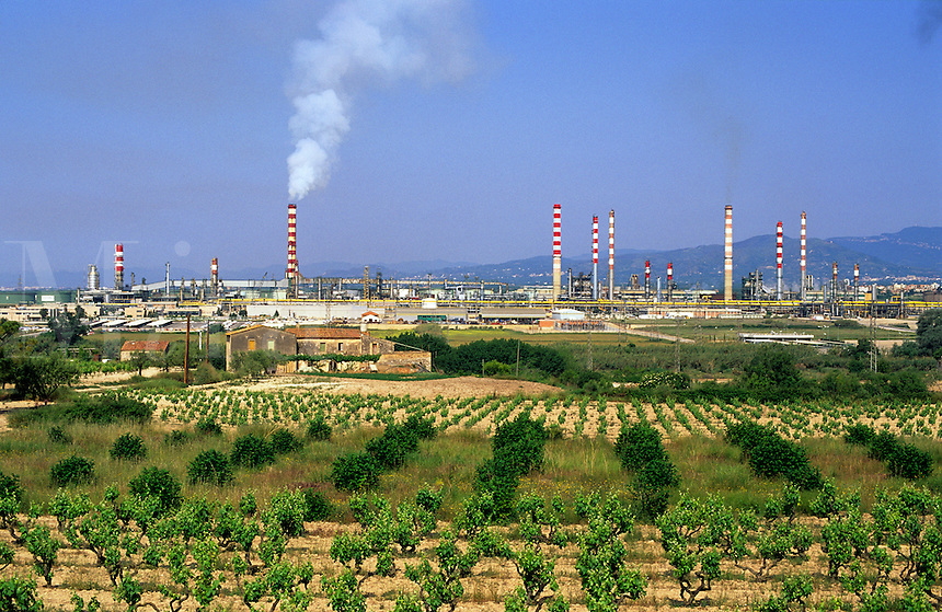 Oil refinery at Tarragona, Catalonia/Catalunya, Spain. Neighbouring farm, farmhouse, vineyards and citrus plantation..