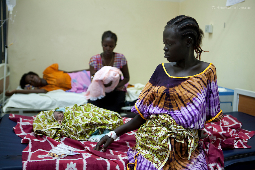 "July 6, 2011 - Juba, Republic of South Sudan - Agnes Gago, a South Sudanese pregnant woman, after giving birth to her second child at the Juba Teaching Hospital, South Sudan's oldest, and by far the largest and best-equipped in the new country. She said, ""I'm not scared but I came to the hospital because I needed help. I can't give birth at home because I'm unable to cut the cord and clean the baby myself. At home there are no facilities and no medications"". South Sudan has the highest maternal mortality rate in the world. One in seven South Sudanese women is likely to die because of complications from delivery. Just 10 per cent of South Sudanese women have access to medical professionals during childbirth. Photo credit: Benedicte Desrus"