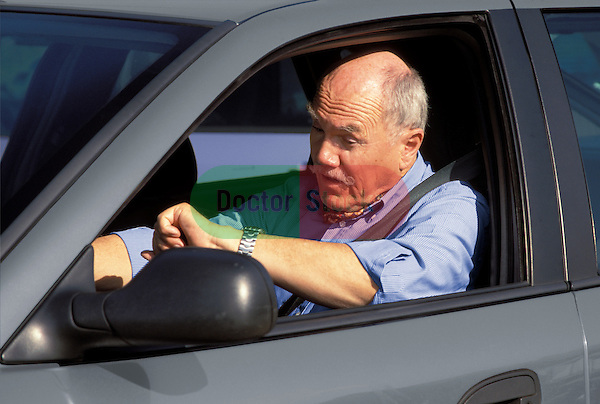 Elderly motorist impatiently checking his watch while caught in traffic