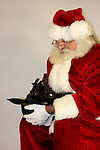 Santa Claus looking into a cowboy hat with two black bunnies