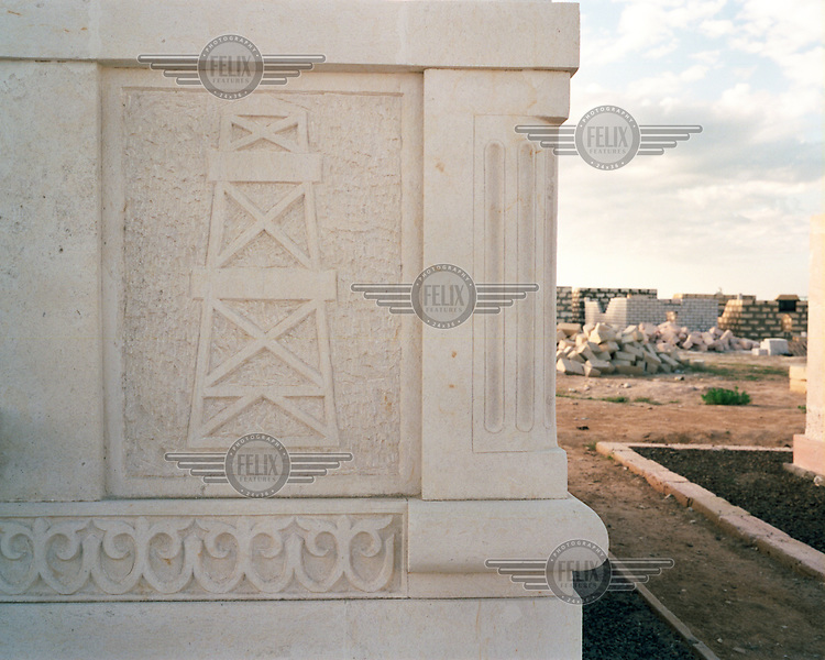 An oilrig is engraved onto the side of a mausoleum, to commemorate a man made wealthy by working in the Caspian oil industry..