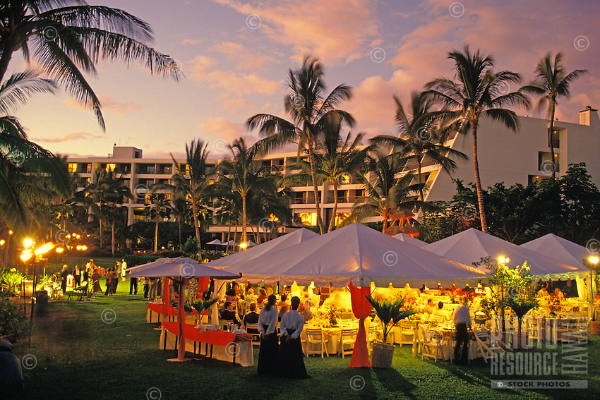 Staff await diners and tents are set up for a banquet, with the hotel and palm trees in the image's background, at the Cuisines of the Sun food festival at the Maunalani Bay Resort on the Big Island in July 2001