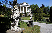 Theatrically posed, classical stone statues grace the formal gardens of this grand Palladian-style property