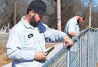 NWA Democrat-Gazette/DAVID GOTTSCHALK Brian Crigler and Bobby Sligar, both with the city of Prairie Grove Street Department, uses tie wires Monday, February 4, 2019, to secure chain link fencing on the top rail of a new section of fencing at Timeless Treasures in Prairie Grove. The city was replacing the fencing after installing new sidewalks on N. Pittman Street.