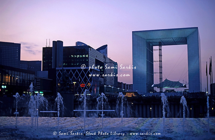 Water fountains in front of the Grande Arche in  La Défense business district at sunset, Paris, France.