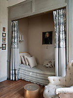 A bed with a striped cover is set in a recess shielded by a curtain in room decorated in tones of grey.