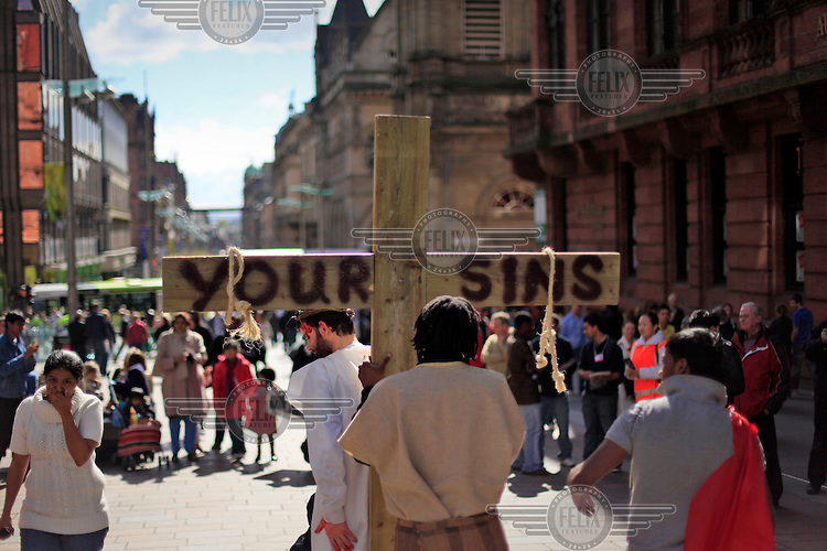 Christians imitate Jesus and carry a cross on Buchanan street in the city centre of Glasgow.