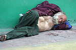 Homeless elderly man asleep on the sidewalk<br />