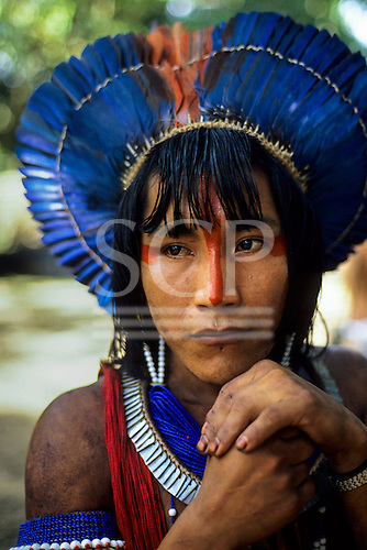 Para State, Brazil. Ta'Kire, a Kayapo Indian warrior with blue feather cocaa headdress at meeting in Altamira, 1989.