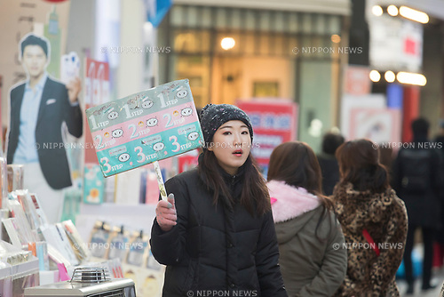 Myeongdong Shopping Street, Mar 7, 2017 : A promoter holds a sign in front of a cosmetics store on Myeongdong shopping street which is famous shopping mecca for tourists from China, Japan and other countries in Seoul, South Korea. China ordered last week their travel agencies to stop selling group tours to South Korea after South Korean defence ministry completed a deal with Lotte Group to deploy a Terminal High Altitude Area Defense (THAAD) battery of the U.S. Army on a Lotte golf course in Seongju, about 260 km southeast of Seoul. The U.S. and South Korea had agreed to station the anti-missile battery with a high-powered radar to counter missile threats from North Korea but China opposed the deployment as they asserted the United States will spy on Chinese military with THAAD. South Korean duty-free shops, hotels and travel agencies will be hit by the travel restrictions of China, local media reported. (Photo by Lee Jae-Won/AFLO) (SOUTH KOREA)