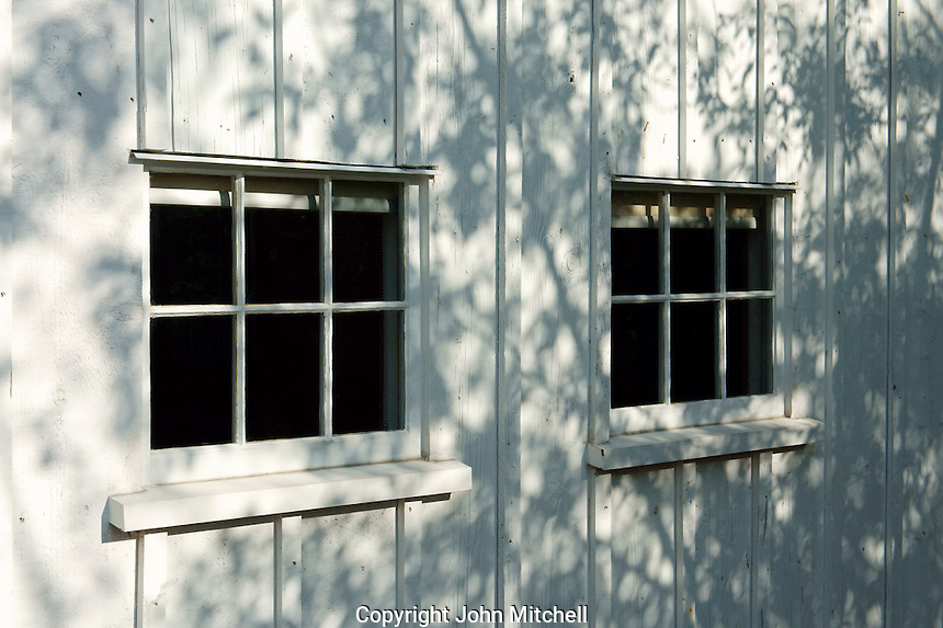 Windows and tree shadows on the wall of a building in the Britannia Heritage Shipyard park, Steveston, British Columbia, Canada